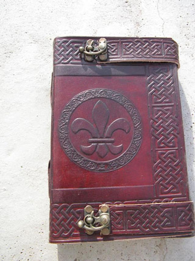Handmade fleur-de-lis leather journal with two latches.